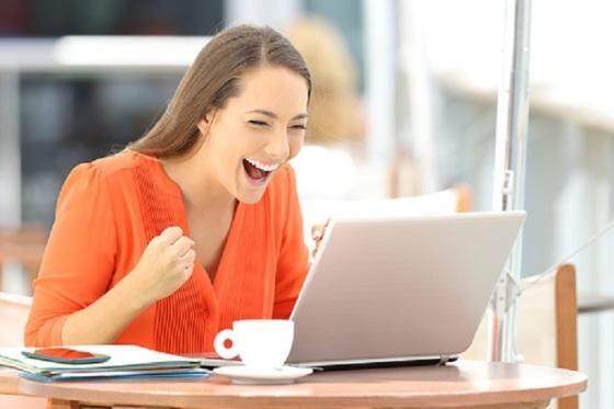 Imagen que muestra una mujer ante un ordenador. La mujer se muestra alegre