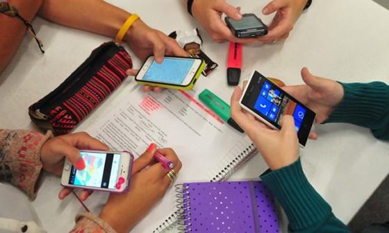 manos de niños en clase con móviles y cuadernos