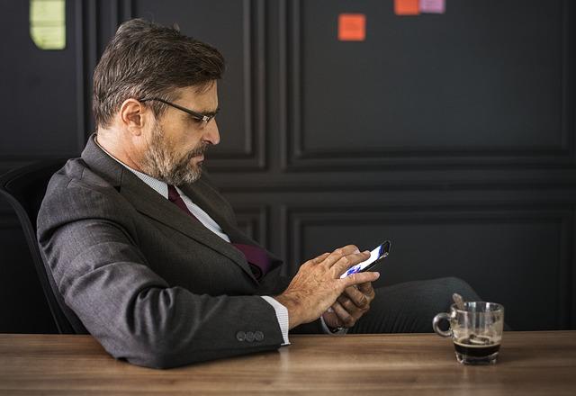 hombre de mediana edad con un dispositivo móvil y una taza de café