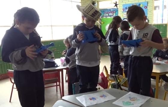 niños y niñas probando realidad aumentada en un salón de clases