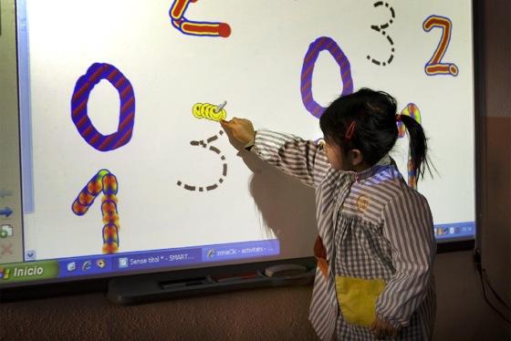 niña ante una pizarra digital en la escuela