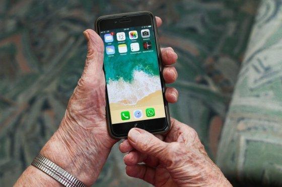 manos de anciana con un teléfono móvil